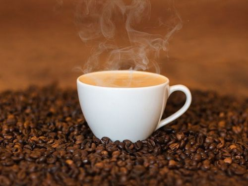 Кофейные зерна и чашка кофе с молоком