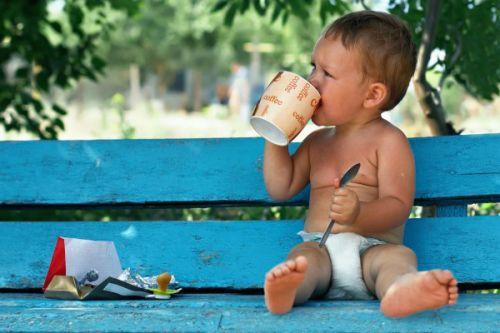 Маленький ребенок пьет кофе