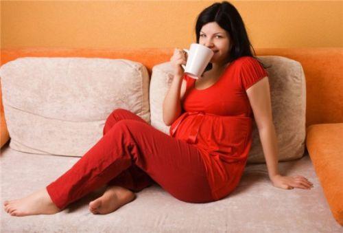 Беременная женщина пьет кофе