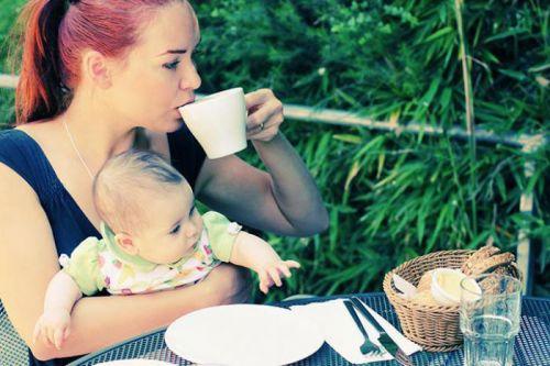 Мама с ребенком на руках пьет чай