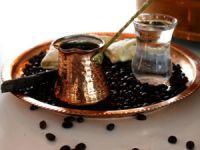 Турка, кофейные зерна и стакан воды